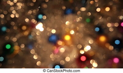 Rotation bokeh from golden tinsel and colorful balls. Christmas and new year background.