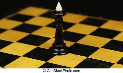 Rotation. Chess figure black king on chess board. Close-up chess figure on chess board.