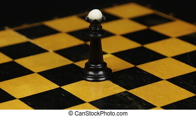 Rotation. Chess figure black queen on chess board. Close-up chess figure on chess board.