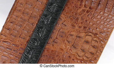 Rotation, close-up of a black strip of skin lying on a brown...