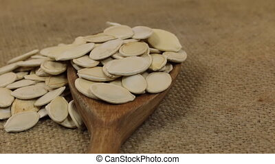 Rotation, heaps of pumpkin seeds, falling from a wooden spoon on burlap.