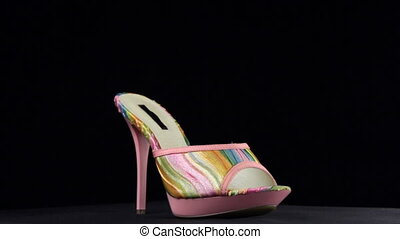 Rotation, high heel clogs. Pink high heel shoes on black background. Full turn of shoes