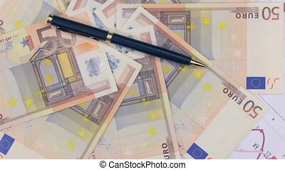 Rotation of a black ballpoint pen lying on the euros.