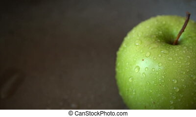 Rotation of a green apple with water drops