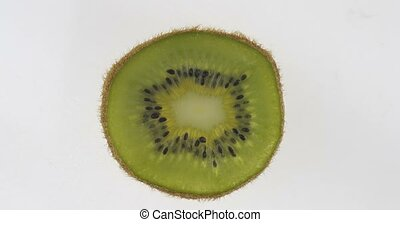 Rotation of a thin transparent kiwi slice. Citrus texture. Top view.