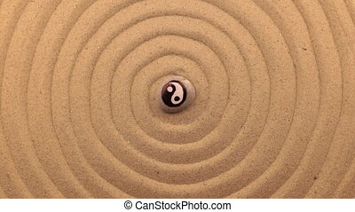Rotation of a white stone with a yin-yang sign, lying in the center of a spiral made of sand.