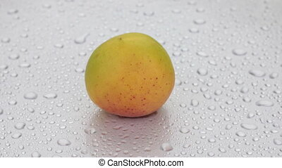Rotation of a whole ripe apricot in drops of dew lying on a...