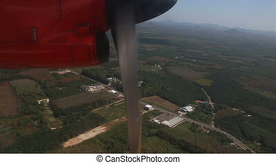 rotation of airplane propeller flying above tropical plantations