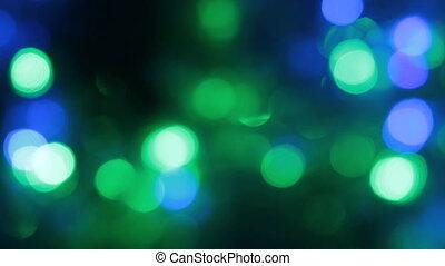Rotation of bokeh, garland flashing lights on a black background.