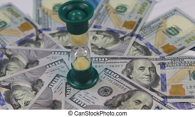 Rotation of hourglasses standing on dollars lying on the...