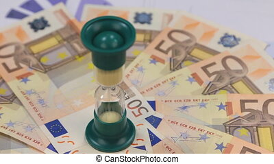 Rotation of hourglasses standing on euros lying on the...