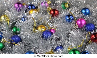 Rotation of multi-colored balls lying on a silvery tinsel....