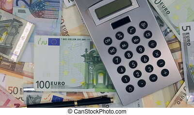 Rotation of the calculator and pen lying on the euros.