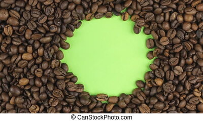 Rotation of the coffee beans lying on a green screen, chroma key.
