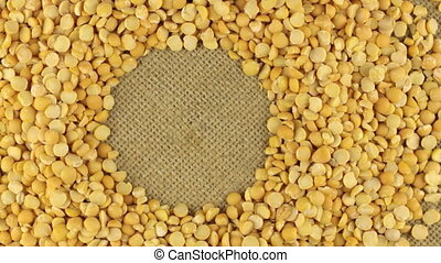 Rotation of the dried peas grains lying on sackcloth with space for your text