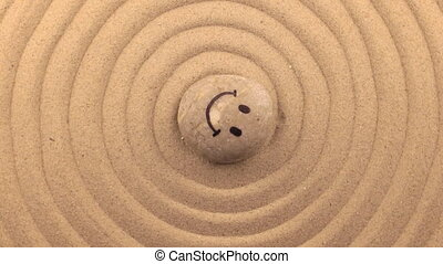 Rotation of the face of the smiley drawn on a white stone lying on the sand.