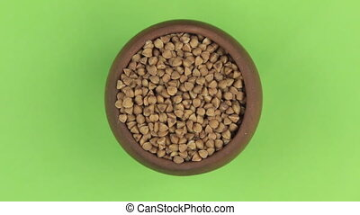 Rotation of the grain of buckwheat in a pot isolated on green screen.