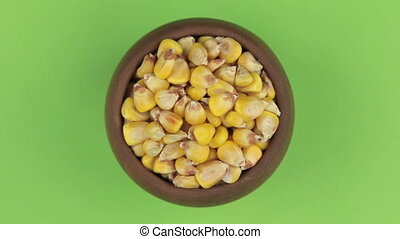 Rotation of the grain of maize in a pot isolated on green screen.