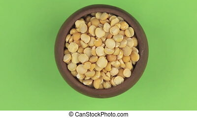 Rotation of the grain of peas in a pot isolated on green screen.