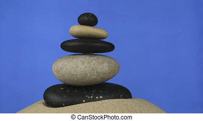 Rotation of the pyramid made of stones standing on the sand....