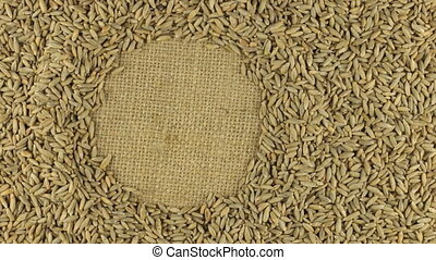 Rotation of the rye grains lying on sackcloth with space for your text