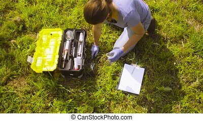 Woman ecologist getting samples of soil. - Rotation. Top...