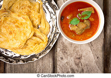 roti canai with spicy curry on old wood, Top view