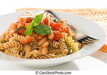 Bowl of rotini pasta with a homemade tomato and bean sauce.