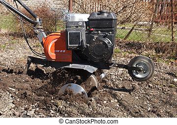 rototiller in the garden - Spring work in a garden. ...