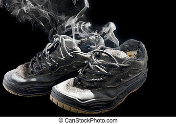 rotten old sneakers - pair of smelly old sneakers on a black...