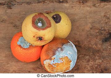 rotten pear and orange fruit on wood vintage