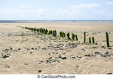 rotting wave breakers at the mouth of the cashen on ballybunion beach on the wild atlantic way