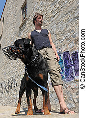rottweiler with his muzzle and young man in city