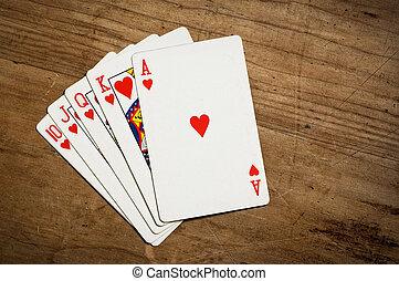Rotyal flush poker hand on table.