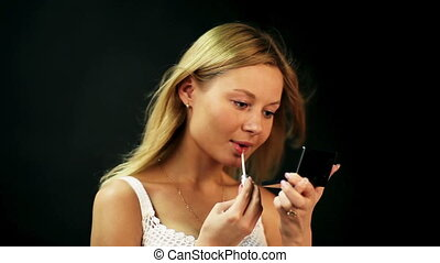 Rouge - Smiling young woman applies rouge on her lips.