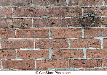 Rough red brick wall with iron link