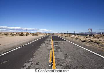 Rough Road - Damaged desert highway in California's harsh...