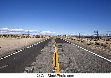 Rough Road - Damaged desert highway in California's harsh...