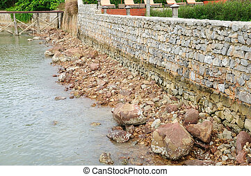 Rough rock beach with stone wall