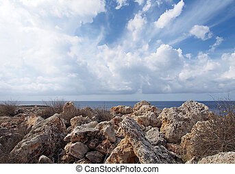 rough rocks and boulders with dry summer vegetation in front of a calm sea with white sunlit clouds filling the sky