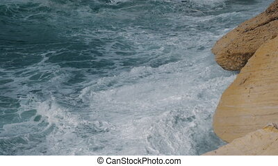 Rough sea and rocks scene - Slow motion shot of sea waves...