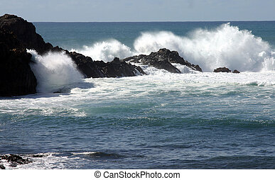 Rough seas on coast - Waves breaking aginsta volcanic...