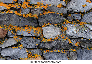 Rough stone wall with lichen