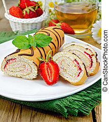 Roulade a cup of tea and strawberries on a board