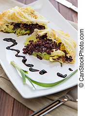 Roulade of cabbage and black rice in a dish