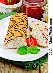 Roulade with jam and strawberries on a board