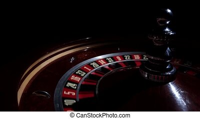 Roulette wheel fast running with white ball, cam moves to...