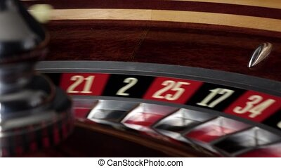 Roulette wheel running and stops with white ball on red -...