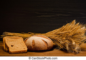 Round and square rye bread, a sheaf on wooden table, black background, space for text