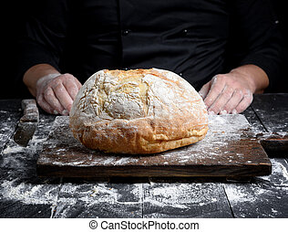 round baked homemade bread on an old brown wooden board
